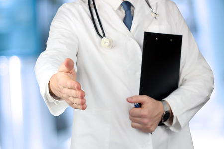 Handshake Gesture from Doctor in  a white  labcoat  and  stethoscope on his sholder