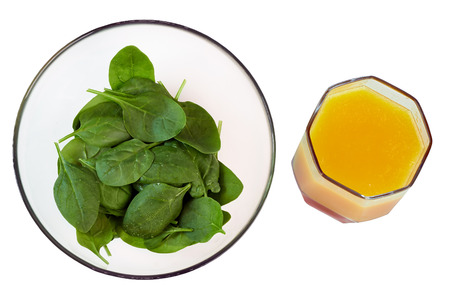 Young  green spinach in a transparent   plate with orange juice , top view, isolated on a white photo