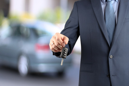 Young successful businessman offering a car key. Close-up of drivers hand showing key Stock Photo