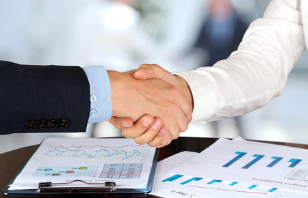 business hands: Close-up image of a firm handshake  between two colleagues in  the office.
