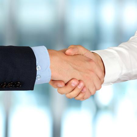 reuniones empresariales: Primer plano imagen de un firme apret�n de manos entre dos colegas en la oficina.