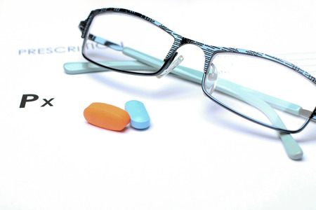 the name of the drug: Empty medical prescription with glasses and pills above
