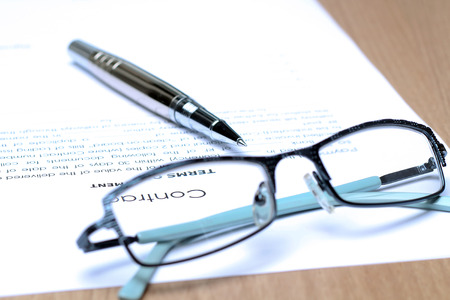 Siver Pen on the contract papers, glasses above Stock Photo