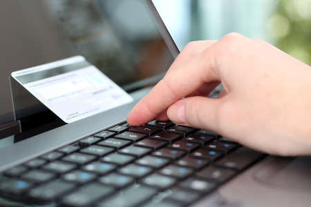 Young business woman  entering  data of  a credit card . On-line shopping on the internet using a laptop photo