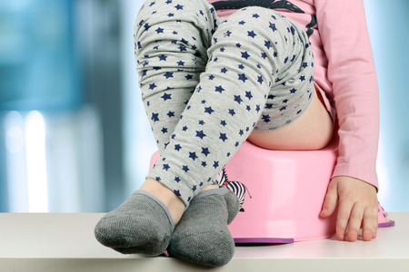 poo: Childrens legs hanging down from a chamber-pot on a blue background