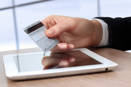 Young business woman  holding  a credit card . On-line shopping on the internet using a tablet photo