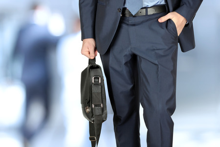 Businessman walking and holding  a  leather briefcase in his hand. Modern city behind Stock Photo