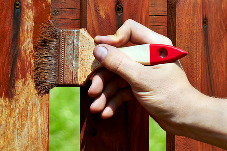 fence: Painting wooden fence with a   brown paint