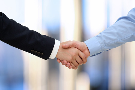 firms: Close-up image of a firm handshake  between two colleagues in office.