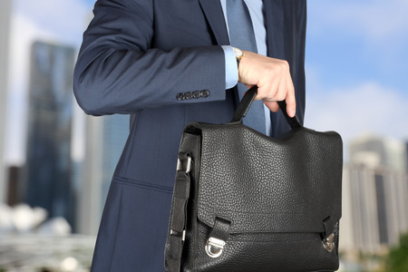leather briefcase: businessman  holding leather briefcase checking time on his watch . Stock Photo