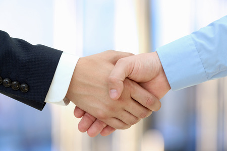 Close-up image of a firm handshake  between two colleagues isolated on a white background Standard-Bild