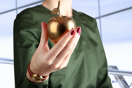 Businesswoman  standing  and holding golden  apple in his hand. photo