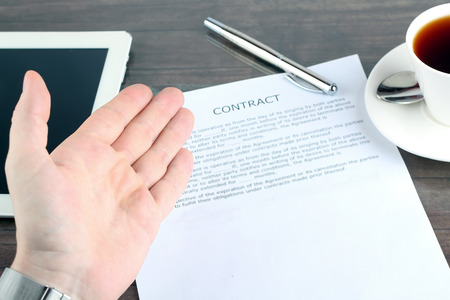 signer: man sitting in a table showing, offering  a contract and where the signer must sign