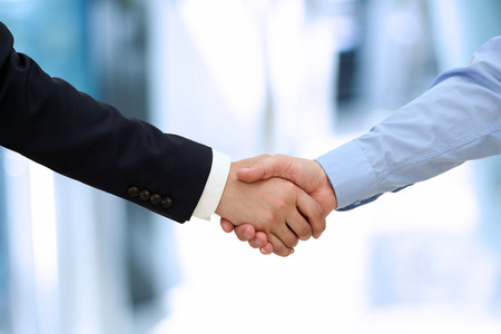 business  deal: Close-up image of a firm handshake  between two colleagues in office.