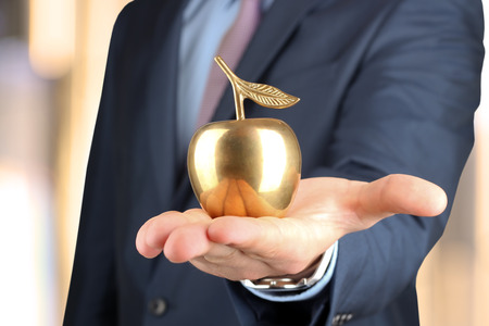 Businessman  standing  and holding golden  apple in his hand. photo