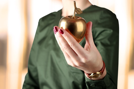 Businesswoman  standing  and holding golden  apple in her hand. photo