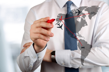 global partnership: Young business man drawing an airplane routes on world map.