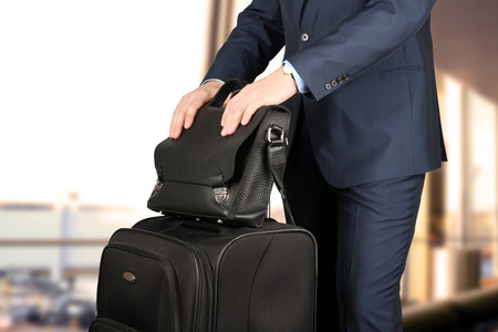 young businessman  in  a modern  stylish suit with  luggage  waiting  for plane in  the airport Standard-Bild