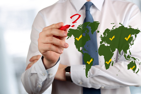 doubtfulness: Young business man drawing  a red  question. Where to go? Stock Photo