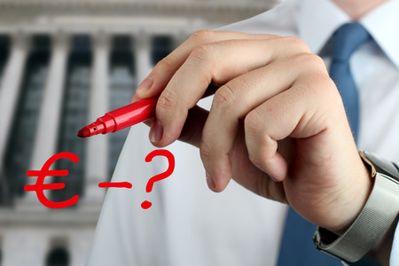 school bills: Man drawing a sign of  euro with question by red pen Stock Photo