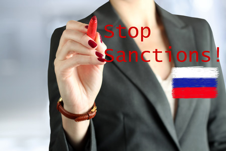 sanctioned: Woman drawing a phrase stop  sanctions  by a  red pen . Flag of Russia behind