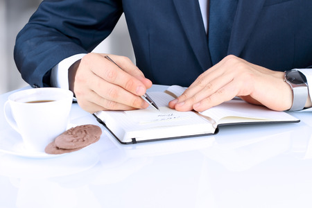 writing pad: The business man writing in the  notebook. A cup of  of coffee with cookies behind