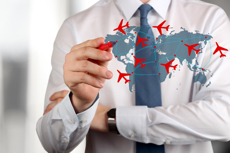 transportation travel: Young business man drawing an airplane routes on world map.