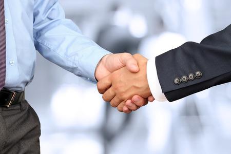 La imagen del primer de un firme apretón de manos entre dos colegas en la oficina. Foto de archivo