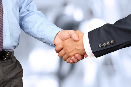 partnership power: The Close-up image of a firm handshake between two colleagues in office.