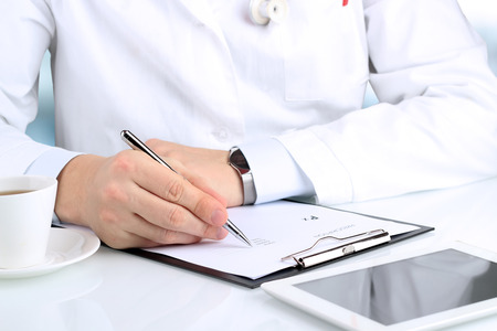 writing pad: Doctor  in a white labcoat writing out RX prescription