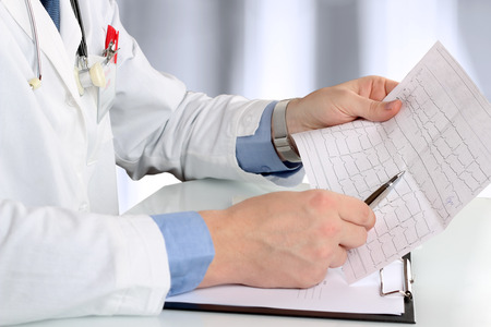 urologist: healthcare and medicine concept -  doctor with clipboard analizing cardiogram