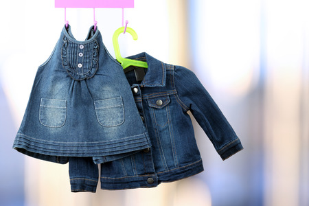 frock coat: Fashion baby  denim dress with  jacket  hanging on a hanger Stock Photo