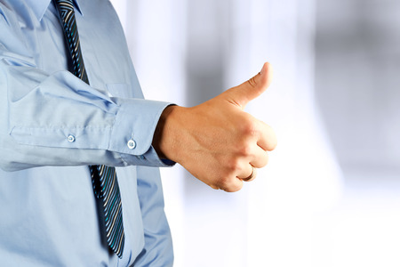 Businessman showing OK sign with his thumb up. photo