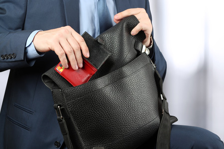 siting: Businessman siting on a chair and putting down a purse to his leather briefcase. Stock Photo