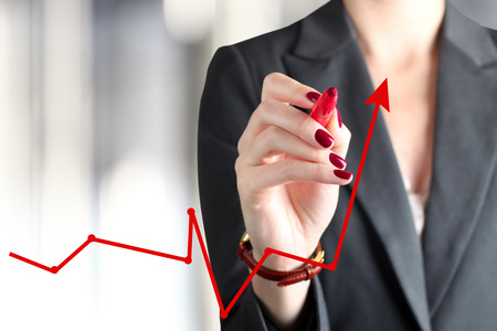 competition success: Businesswoman drawing a virtual graph by a red pen