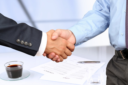 The Close-up image of a firm handshake between two colleagues under contract