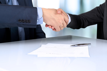 autograph: Close-up image of a firm handshake between two colleagues after signing a conntract