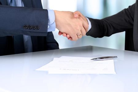contrato de trabajo: Primer plano imagen de un firme apretón de manos entre dos colegas después de firmar un conntract Foto de archivo
