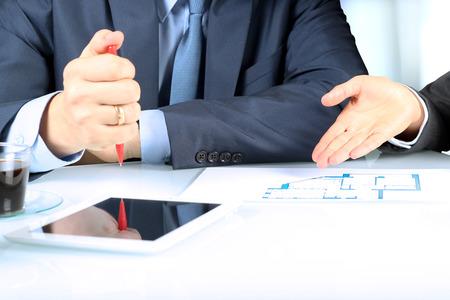 bienes raices: Agente de bienes raíces que muestra los planes de vivienda a un businesssman. Centrarse en una mano