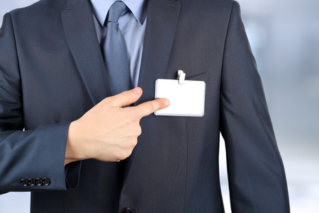 The business man showing a  Blank Badge photo