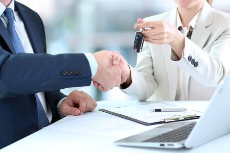 Auto Verkäuferin Übergabe der Schlüssel für ein neues Auto, um einem jungen Geschäftsmann. Handshake zwischen zwei Geschäftsleuten Standard-Bild - 41924386