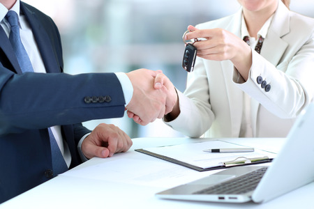 Car saleswoman handing over the keys for a new car to a young businessman . Handshake between two business people Stock Photo