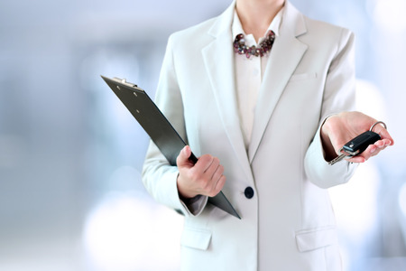 ownership and control: Young successful businesswoman offering a car key. Stock Photo