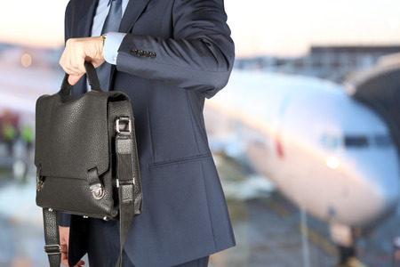 businessman  holding leather briefcase checking time on his watch at the airport Standard-Bild