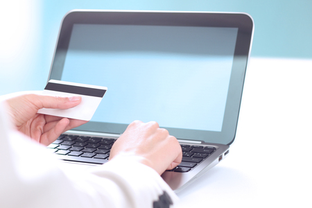 debet: Young business woman  entering  data of  a credit card . On-line shopping on the internet using a laptop Stock Photo