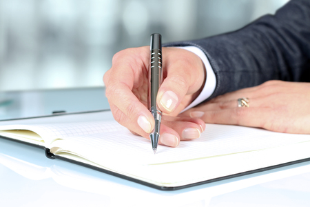noting: Womans hand using a pen noting on notepad Stock Photo