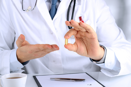 labcoat: Doctor in a white  labcoat giving a pill Stock Photo