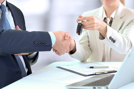 car key: Car saleswoman handing over the keys for a new car to a young businessman . Handshake between two business people Stock Photo