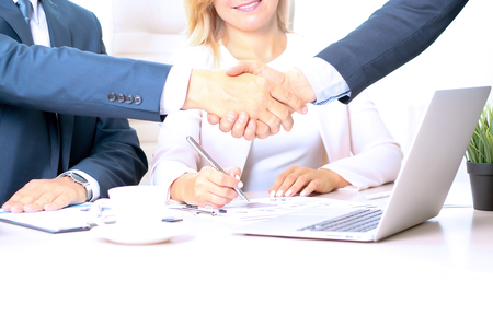 handshaking: Image of business partners handshaking over business objects on workplace