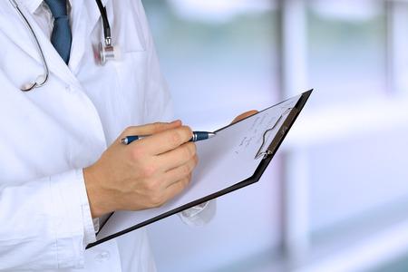 estudiantes medicina: joven m�dico con un estetoscopio alrededor de su cuello que sostiene una carpeta negro
